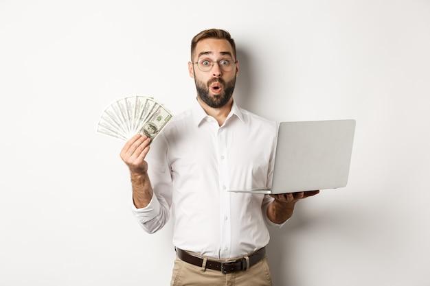 Affaires Et Commerce électronique. Homme à La Recherche D'un Revenu D'argent, Travaillant En Ligne, à L'aide D'un Ordinateur Portable, Debout Photo gratuit