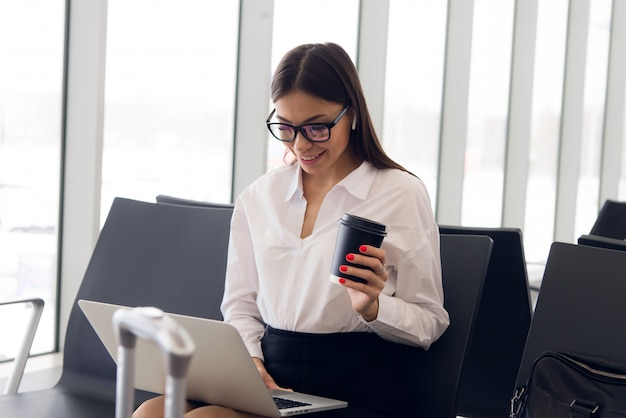 Affaires De Pause. Belle Femme D'affaires Travaillant Sur Ordinateur Portable En Attendant Son Vol Dans Un Aéroport Photo Premium