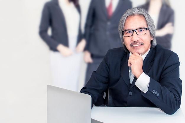 Affaires senior vieil homme sérieux au bureau. il a l'air souriant Photo Premium