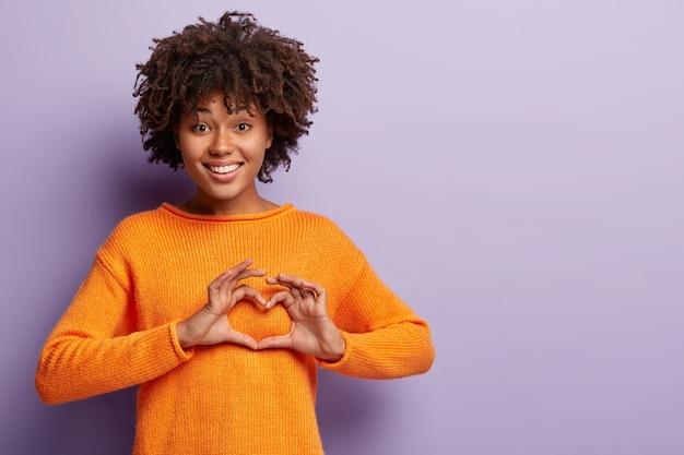 Affectionale Belle Femme A Le Cœur Plein D'amour, Montre Le Signe De La Saint-valentin, Vêtue D'un Pull Orange Décontracté Photo gratuit