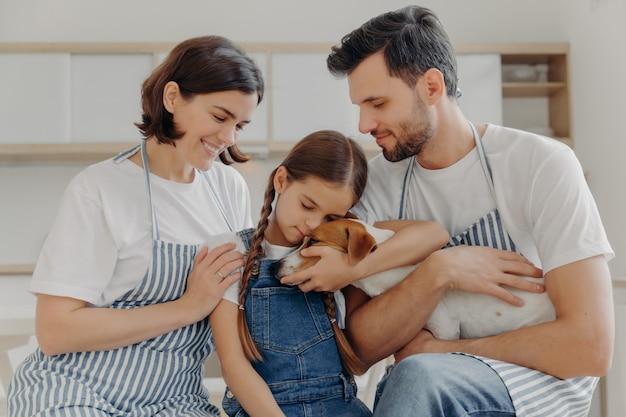 Affectueuse Petite Fille Embrasse Le Chien De Race Avec Amour, Mère Et Père. Famille Heureuse Et Leur Animal De Compagnie Photo Premium