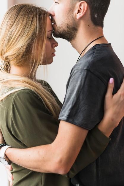 Affectueux jeune homme embrasser sa copine sur le front Photo gratuit