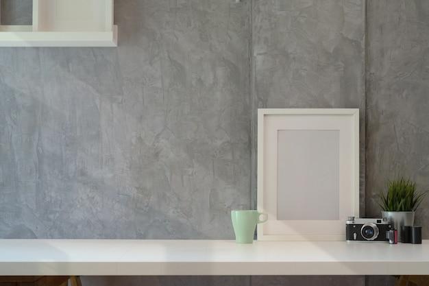 Affiche de la maquette avec caméra vantage sur l'espace de bureau en bois blanc et espace de copie. Photo Premium