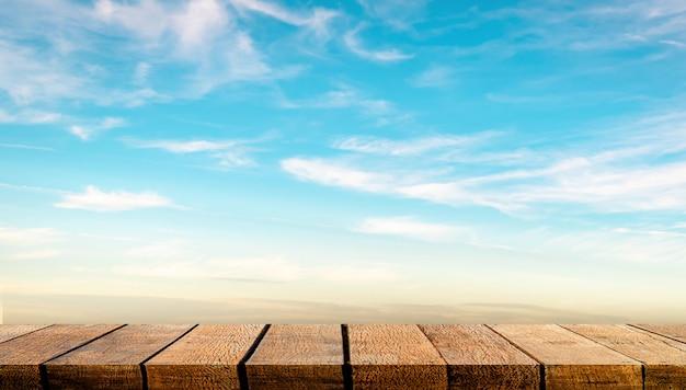 Afficher Le Comptoir De La Table D'étagère En Bois Avec Espace De Copie Pour La Toile De Fond Et L'arrière-plan Publicitaire Avec Fond De Ciel Clair De Nuage Bleu Photo Premium