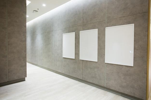 Affiches carrées vierges sur un mur de béton dans la salle vide Photo Premium