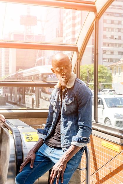 Africain élégant jeune homme assis à l'entrée du métro dans la ville Photo gratuit