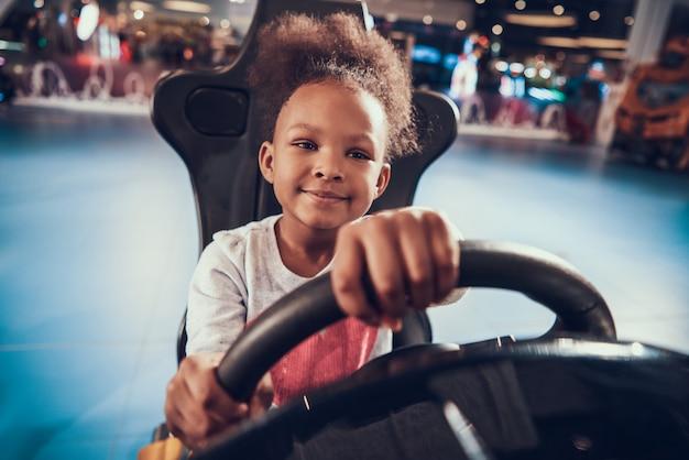 African american kid jouant à un jeu de simulateur de course Photo Premium