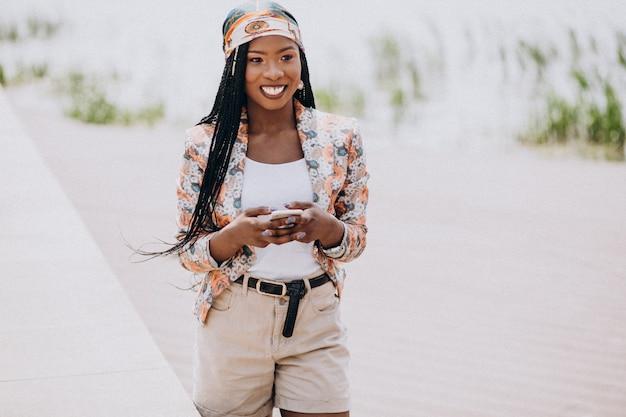 Afro-américain à l'aide de téléphone dans le parc Photo gratuit