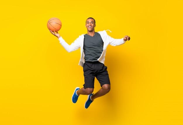 Afro-américain basketteur homme isolé sur jaune Photo Premium