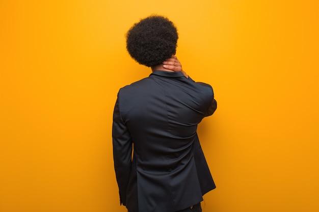 Afro-américain jeune entreprise sur un mur orange par derrière penser à quelque chose Photo Premium