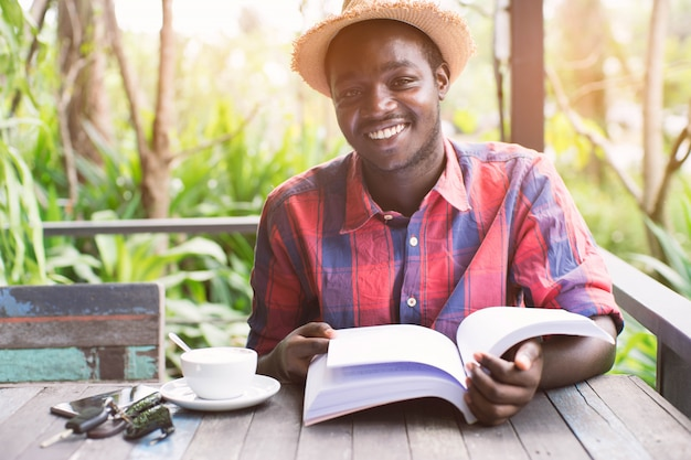 Afro-américain, lisant un livre avec café, clé et smartphone. Photo Premium