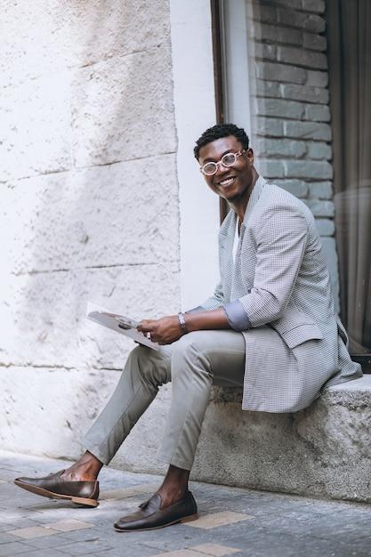 Afro-américain lisant un magazine Photo gratuit