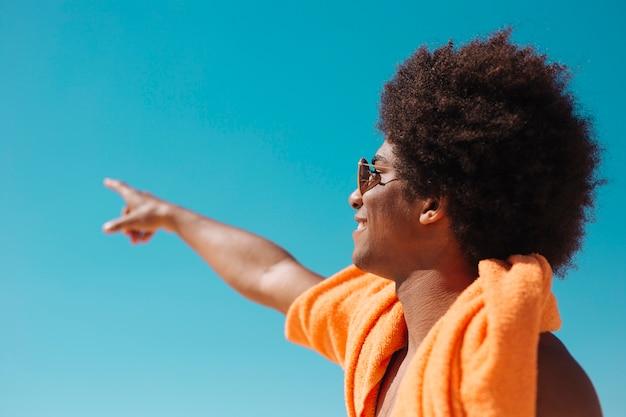 Afro-américain pointant vers le ciel Photo gratuit