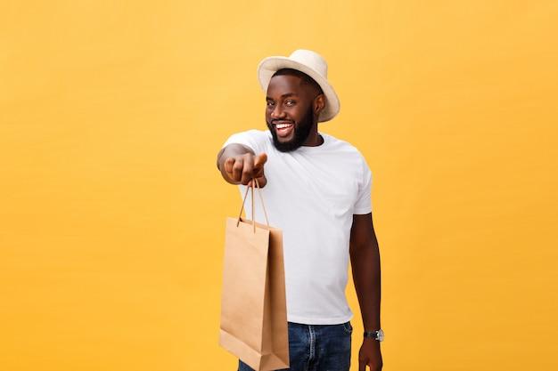 Afro-américain Avec Des Sacs En Papier Coloré Isolé Sur Fond Jaune Photo Premium