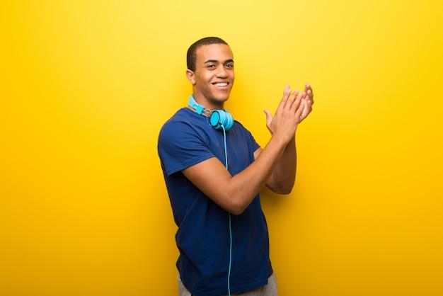 Afro-américain avec t-shirt bleu sur fond jaune applaudir après la présentation à une conférence Photo Premium
