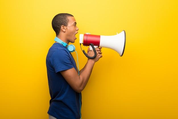 Afro-américain avec un t-shirt bleu sur fond jaune en criant Photo Premium