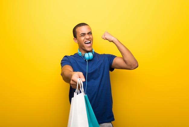 Afro-américain Avec Un T-shirt Bleu Sur Fond Jaune Tenant Beaucoup De Sacs Photo Premium
