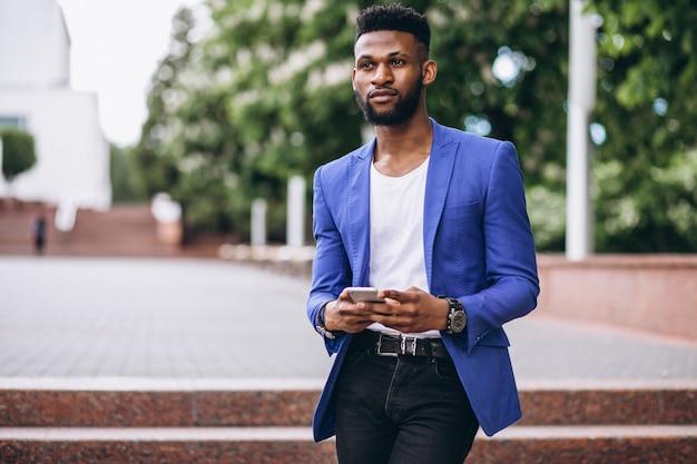 Afro-américain en veste bleue à l'aide de téléphone Photo gratuit