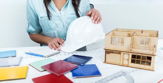 Afro-américaine dame sur une chaise tenant un casque de sécurité près du plan et modèle de maison sur la table Photo gratuit