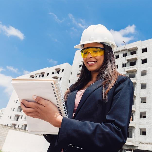 Afro-américaine dans un casque de sécurité avec un ordinateur portable près du bâtiment en construction Photo gratuit