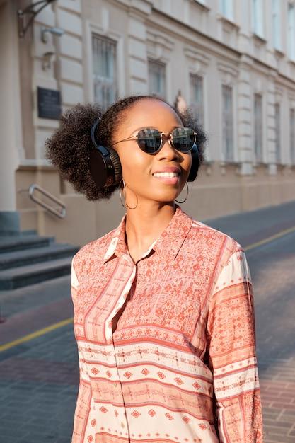 Une afro-américaine noire se promène en ville le soir et écoute de la musique au casque. fille à lunettes de soleil en été sourit et regardant le coucher du soleil. Photo Premium
