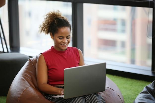Afro-américaine en regardant son ordinateur portable dans un café Photo Premium
