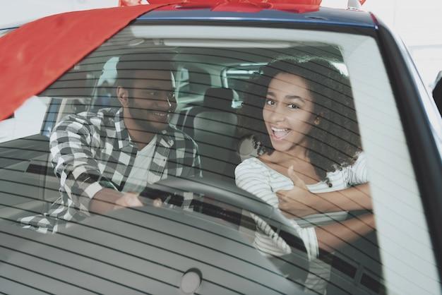 Afro couple à l'intérieur de la voiture fille au volant. Photo Premium