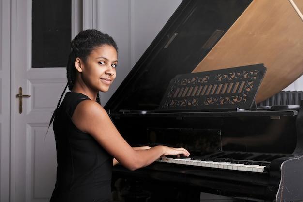 Afro femme jouant au piano Photo Premium