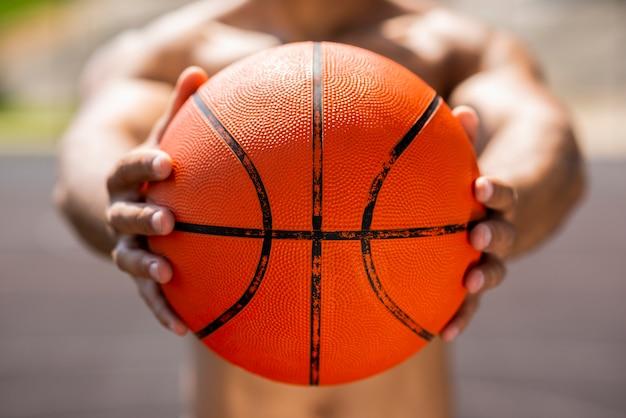 Afro homme tenant un ballon de basket Photo gratuit