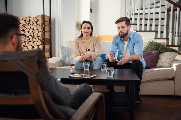 Agacé Couple Caucasien D'homme Et Femme Ayant Une Conversation Avec Un Psychologue Sur La Séance De Thérapie Dans La Salle Lumineuse. Photo Premium