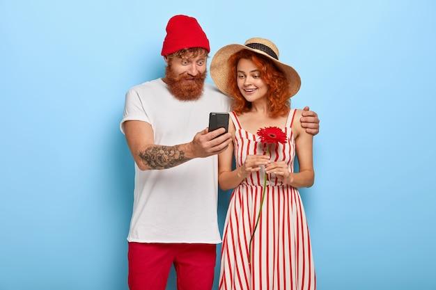 L'âge Des Smartphones. Jeune Couple Heureux Regarder Du Contenu En Ligne Via Smartphone Photo gratuit
