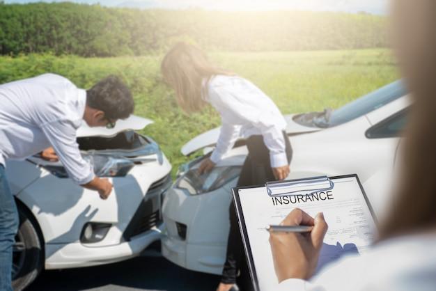 Agent d'assurance écrit sur le presse-papiers après les voitures accidentées. Photo Premium