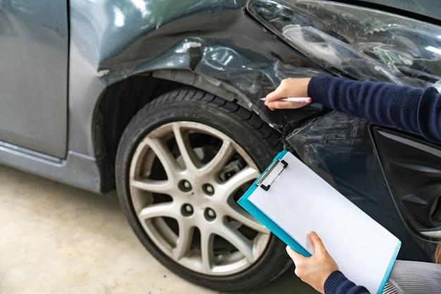 Un agent d'assurance examine un véhicule endommagé et dépose un formulaire de réclamation après accident Photo Premium