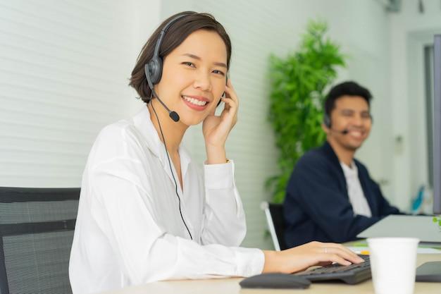 Agent De Centre D'appel Asiatique Femme Souriant Travaillant En Salle D'opération à Table De Bureau Photo Premium