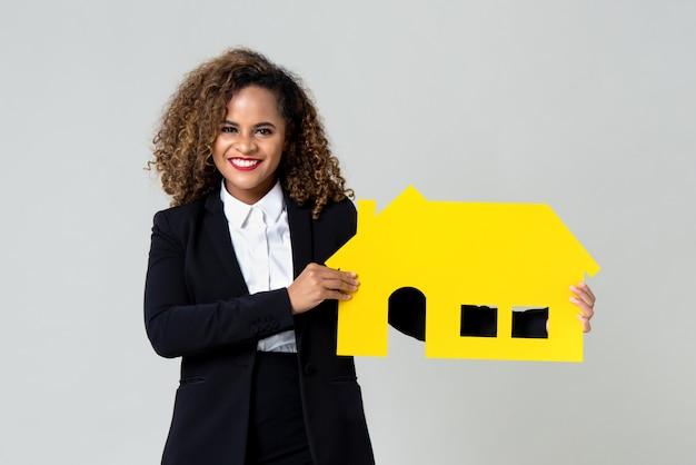 Agent heureux tenant la maison jaune Photo Premium