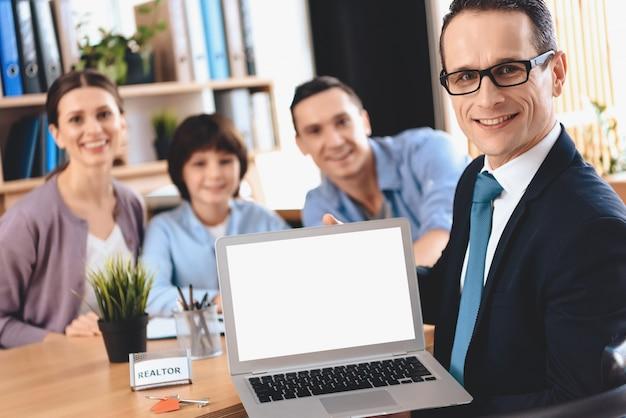 Agent immobilier assis au bureau et présentant un ordinateur portable. Photo Premium