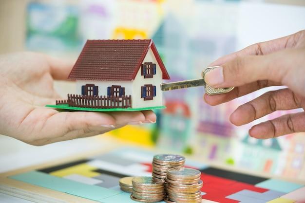 Agent immobilier et client échangeant modèle de maison et clé en main. Photo Premium