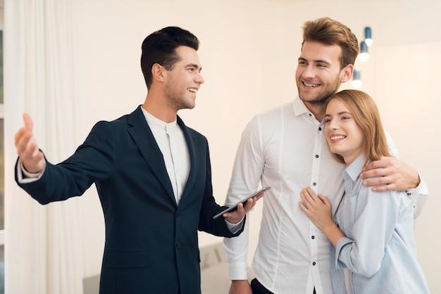 Agent immobilier en costume montre un nouvel appartement aux clients. Photo Premium