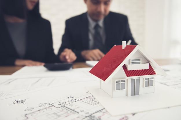 Agent Immobilier Discutant Du Travail Avec Les Plans Et Le Modèle De Maison Sur La Table Photo Premium