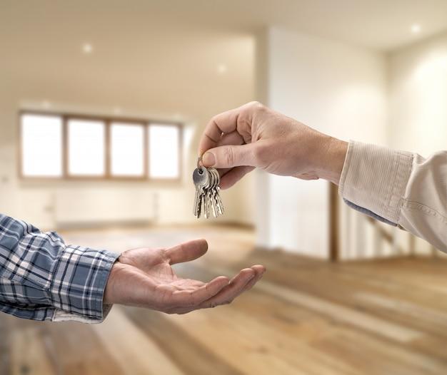 Agent immobilier donnant la clé de la maison à l'acheteur dans une pièce vide Photo Premium