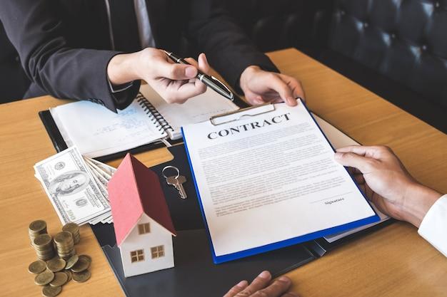 Agent immobilier donnant un stylo à un client signant un contrat de contrat d'immobilier avec un formulaire de demande de prêt hypothécaire approuvé, achetant ou concernant une offre de prêt hypothécaire et une assurance habitation Photo Premium