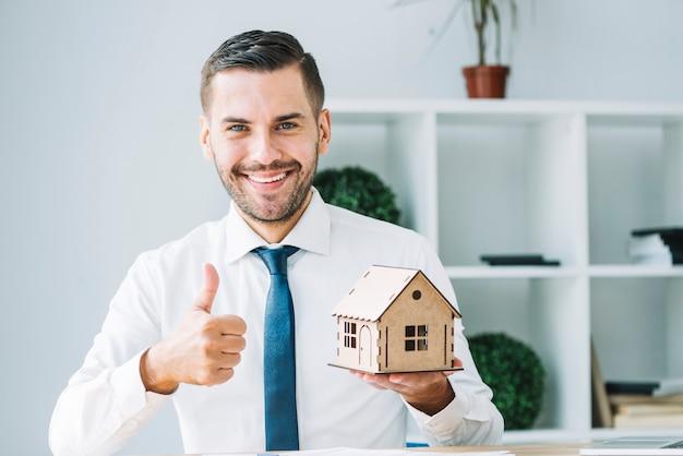 Agent immobilier avec la maison de jouet gesticulant thumb-up Photo gratuit