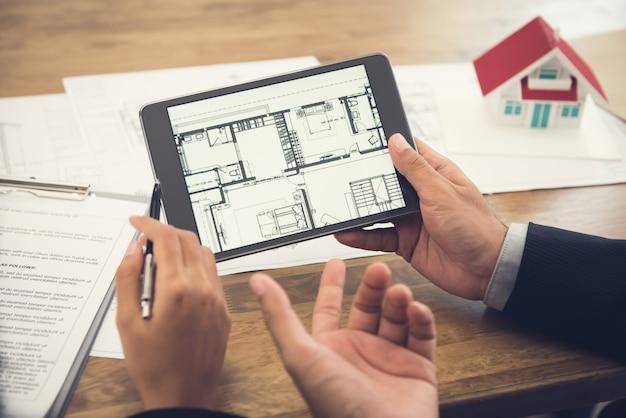 Agent Immobilier Présentant Le Plan D'étage Au Client Sur Une Tablette Photo Premium