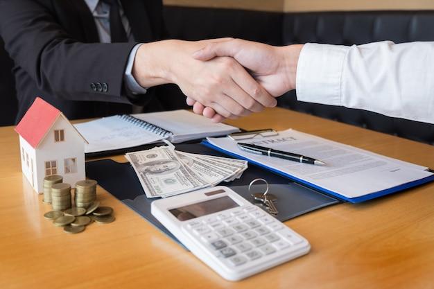 Agent promoteur immobilier et signe sur le document donnant les clés de la nouvelle maison Photo Premium
