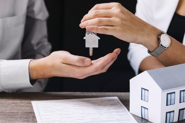 Agent de récolte donnant une nouvelle clé d'appartement Photo gratuit
