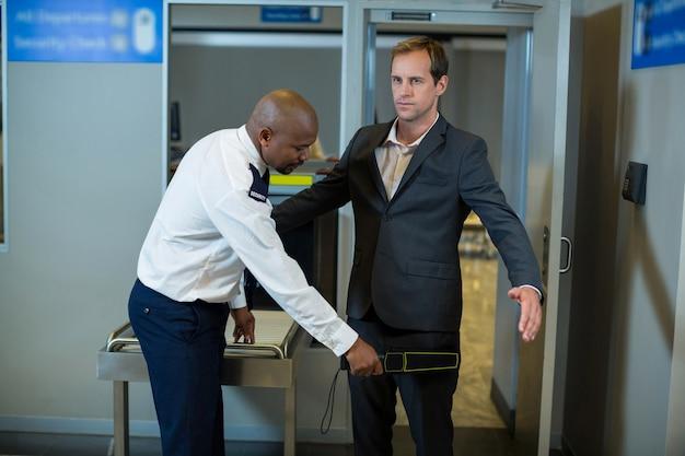 Agent De Sécurité De L'aéroport à L'aide D'un Détecteur De Métaux à Main Pour Vérifier Un Banlieusard Photo gratuit