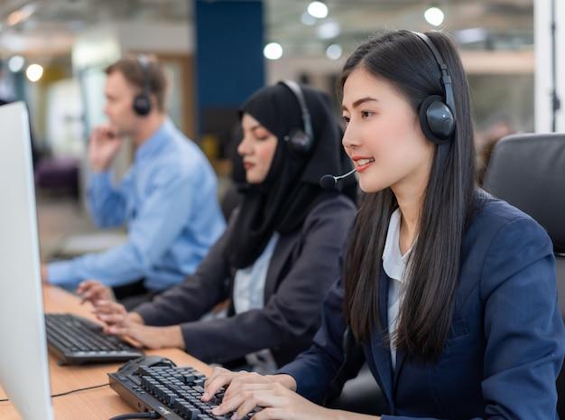Agent de service clientèle femme asiatique souriant heureux avec casques d'écoute Photo Premium