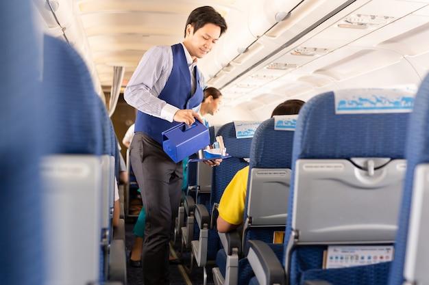 L'agente de bord de bangkok airways sert des boissons aux passagers à bord. Photo Premium