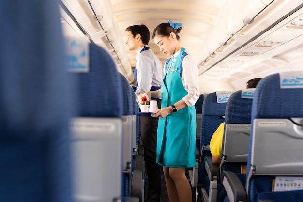 L'agente de bord de bangkok airways sert de la nourriture aux passagers à bord. Photo Premium
