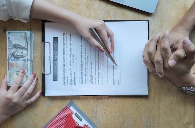 Des agents d'assurances discutant avec leurs clients de la signature d'un contrat d'achat d'assurance habitation. concepts d'accord. Photo Premium